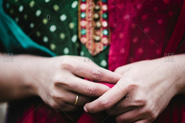 Midsection of woman in salwar kameez with hands clasped