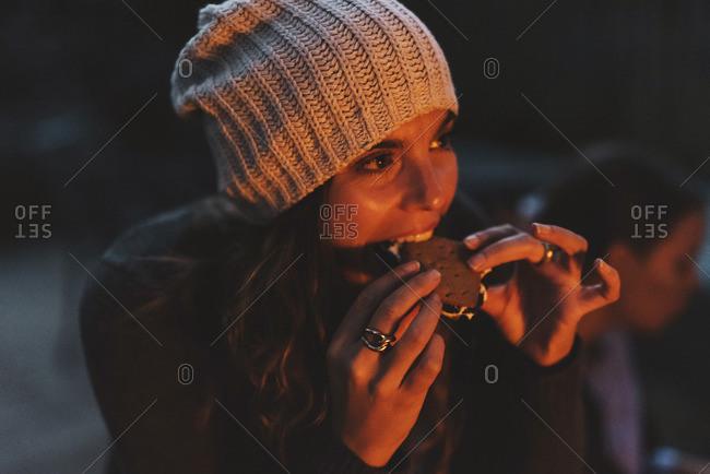 Woman eating smore while sitting in backyard at night