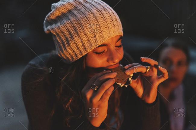 Woman enjoying smore while sitting in backyard at night