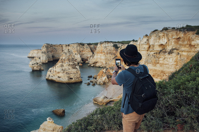 Hiker photographing mountains by sea through smart phone at Praia da Marinha