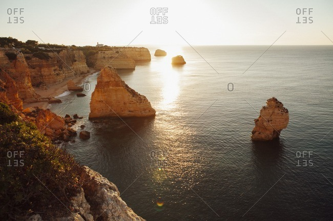 Scenic view of mountains by sea against sky at Praia da Marinha during sunset