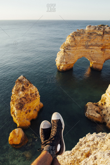 Low section of man wearing shoes resting on cliff against sea
