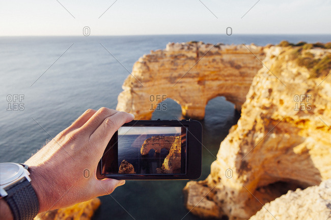 Cropped image of man photographing natural arch through phone at Praia da Marinha