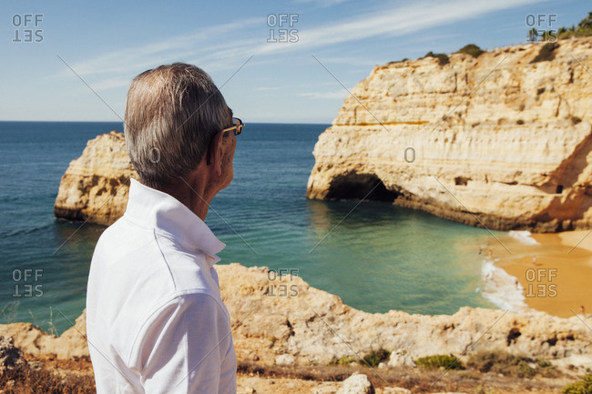Senior man looking at sea while standing on cliff against sky