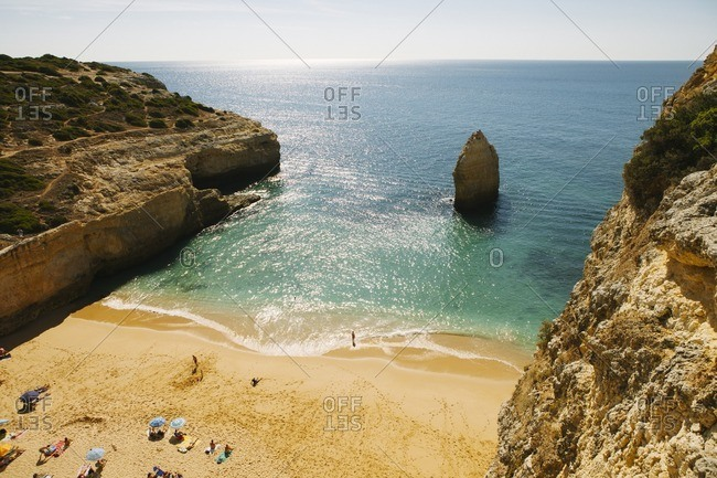 Scenic view of beach by cliff against sky at Praia da Marinha