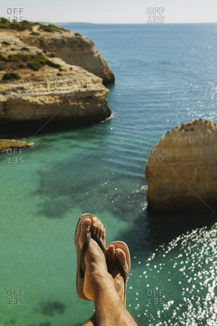 Low section of man wearing slippers resting on cliff against sea