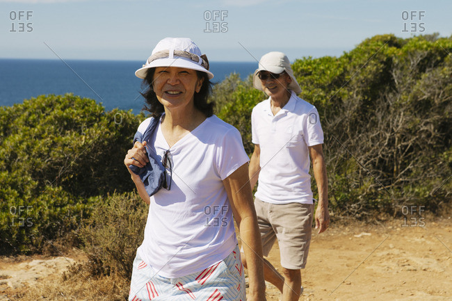 Senior couple walking on cliff against sea