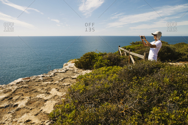 Man photographing sea through phone while standing on cliff against sky