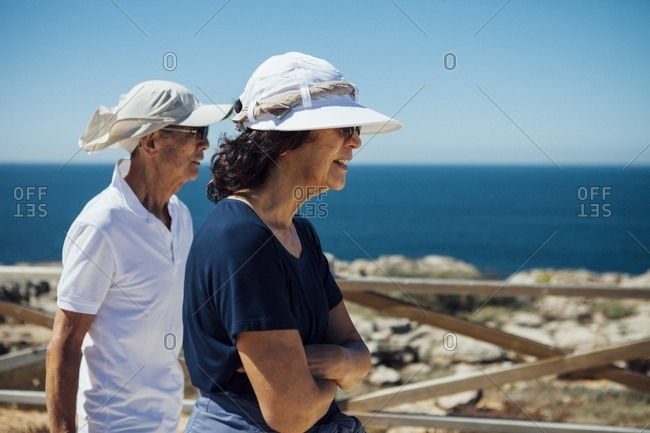 Senior couple looking at sea while standing by railing against clear sky