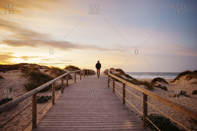 Distant view of hiker walking on footbridge at beach against sky during sunset