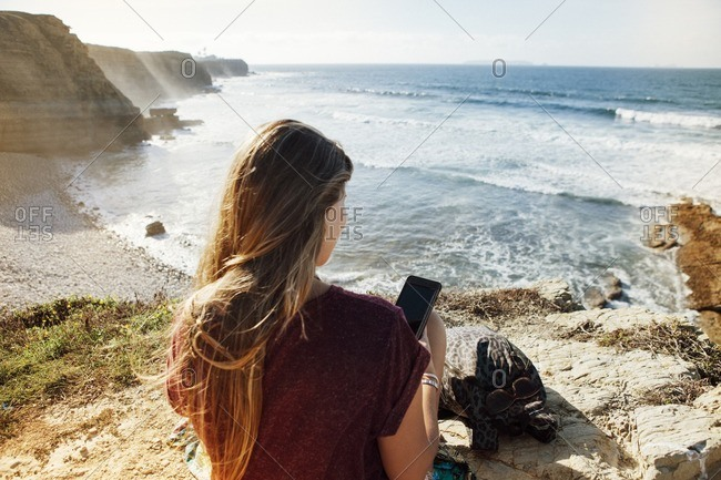 Rear view of woman using mobile phone while sitting on cliff by sea