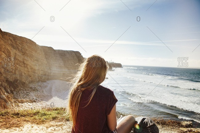 Rear view of woman relaxing at beach on sunny day