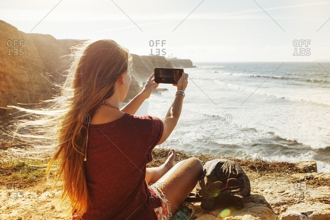 Rear view of woman photographing while sitting on cliff by sea