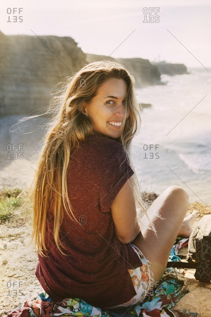 Portrait of happy woman sitting on cliff by sea against sky