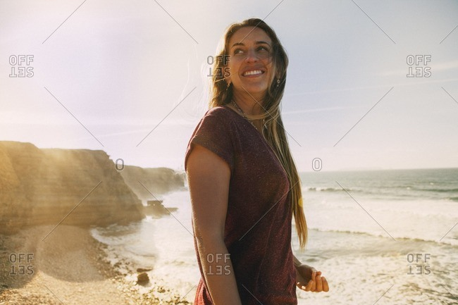 Smiling woman looking away while standing at beach against sky