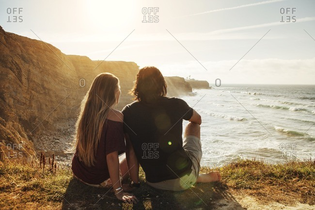 Rear view of couple sitting on cliff and looking at sea