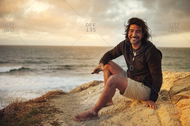Portrait of happy man holding mobile phone while sitting on cliff by sea