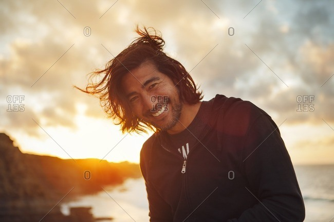 Portrait of smiling man standing at beach against cloudy sky