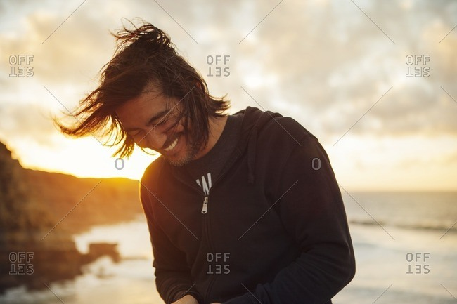 Happy man smiling while standing at beach against cloudy sky during sunset