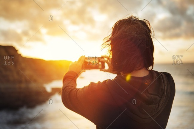 Rear view of man photographing while standing at beach during sunset