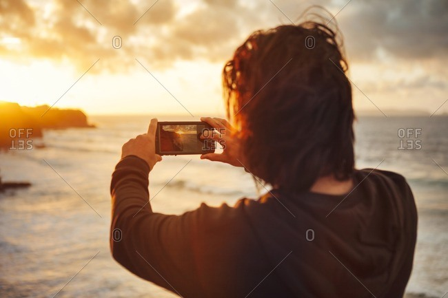 Rear view of man photographing sea during sunset