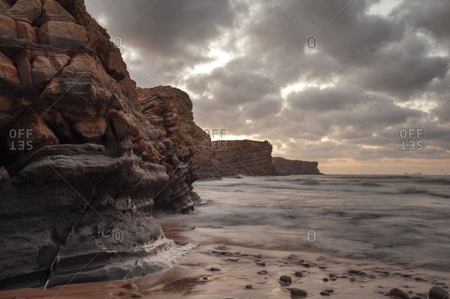 Scenic view of sea by rock formation against cloudy sky