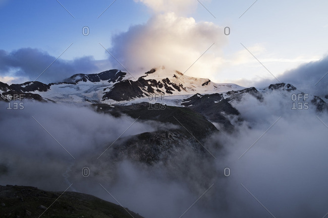 Scenic view of snowcapped mountain covered in clouds