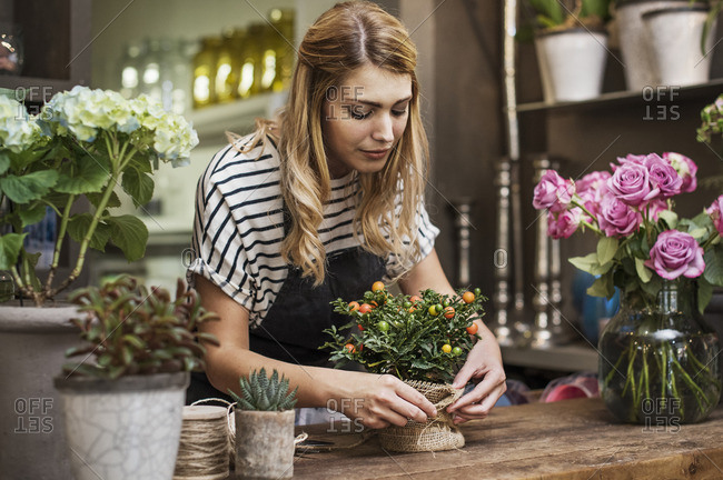 Florist arranging flowers at table in shop