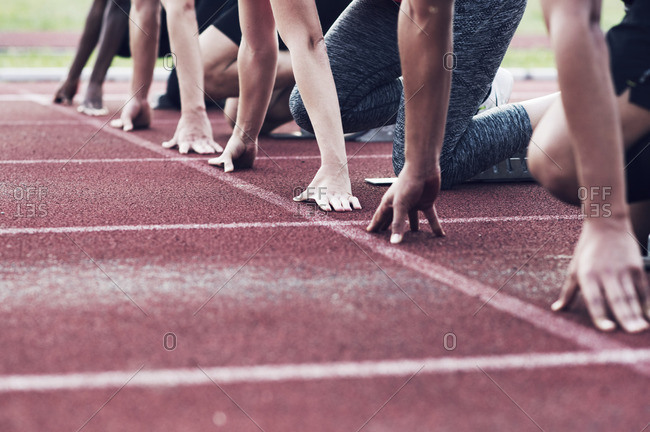 Cropped image of runners poised at starting blocks on track