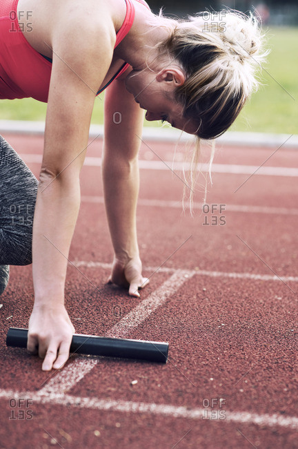 Athlete with relay baton on track