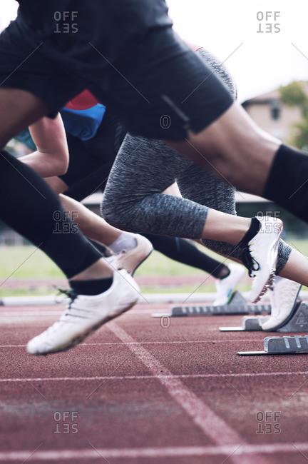 Athletes sprinting from starting blocks on track