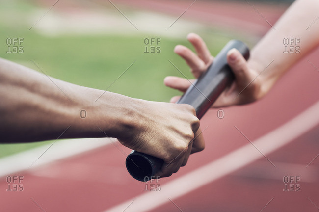 Cropped image of runner passing baton to teammate