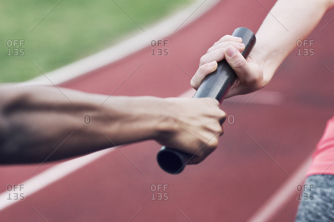 Cropped image of woman passing baton to teammate