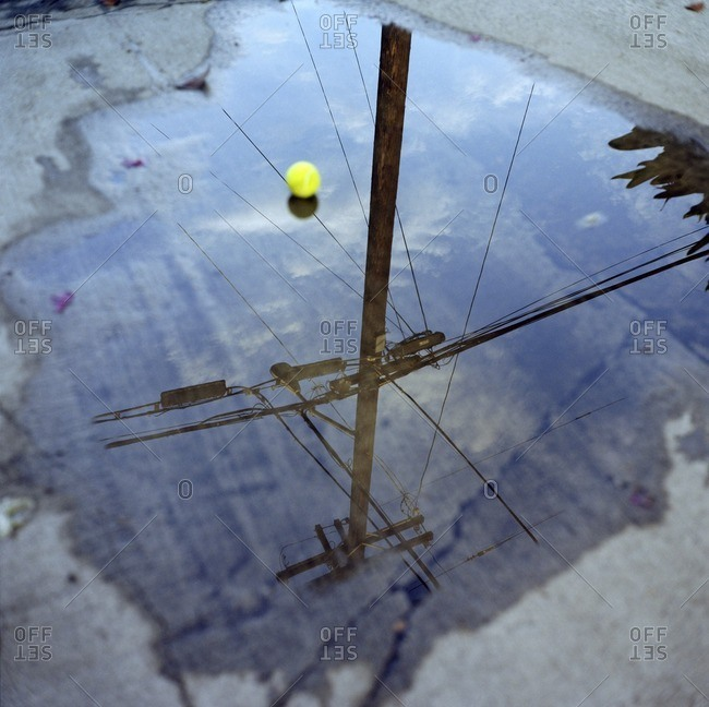 High angle view of ball and electricity pylon reflection in puddle on street