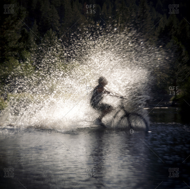 Water splashing while person cycling in puddle