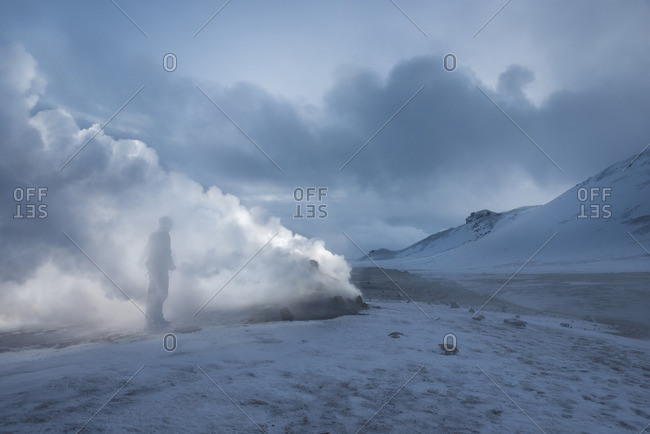 Man standing by fumaroles emitting steam on snow covered field