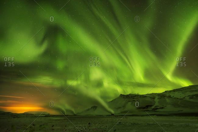 Scenic view of aurora borealis over mountains