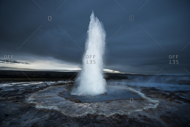Strokkur geyser erupting against cloudscape