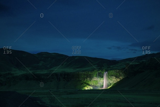 Distant view of waterfall amidst green landscape