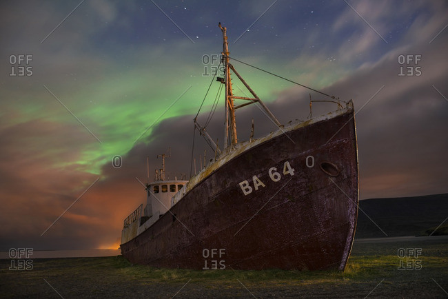 Old ship on field against dramatic sky