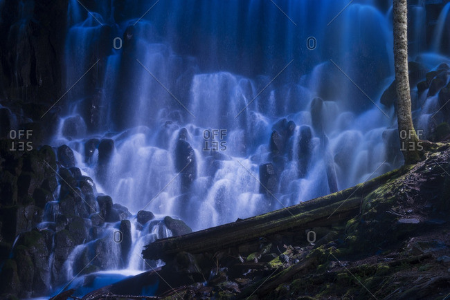 Scenic view of waterfall over rocks at dusk