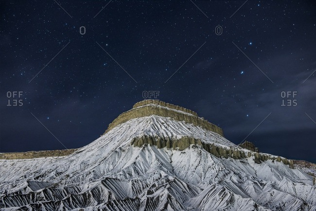 Scenic view of snowcapped mountain against starry sky at night