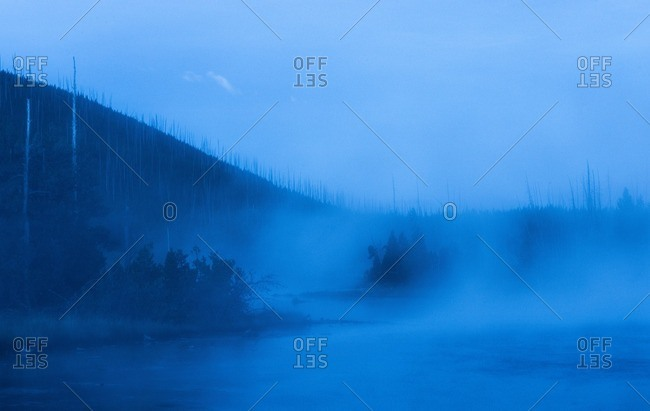Scenic view of lake against mountain during foggy weather at dusk