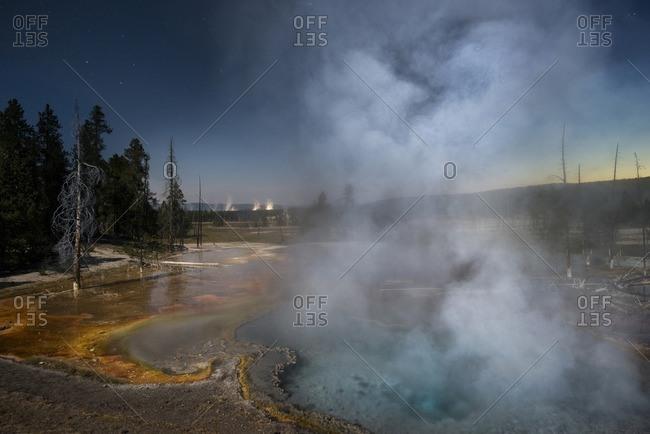 Steam emitting from geyser against sky at dusk
