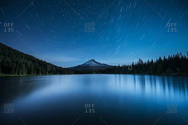 Scenic view of lake against star trails in sky at night