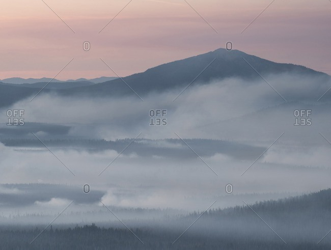 Scenic view of clouds covering mountain during sunset