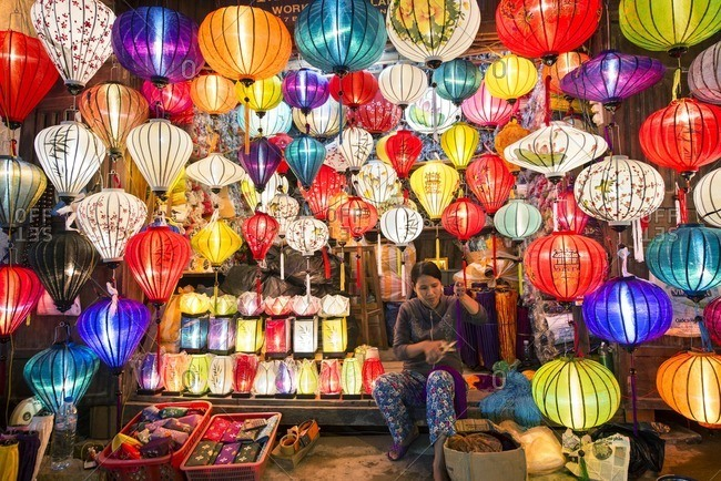Vietnam - October 27, 2013: Owner selling various multi-colored lanterns in shop