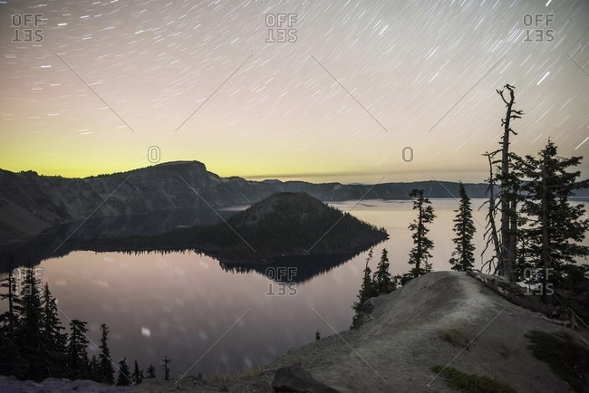 Scenic view of lake against star trails in sky during sunset