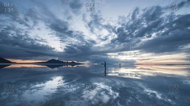 Silhouette people standing on Bonneville Salt Flats against cloudy sky