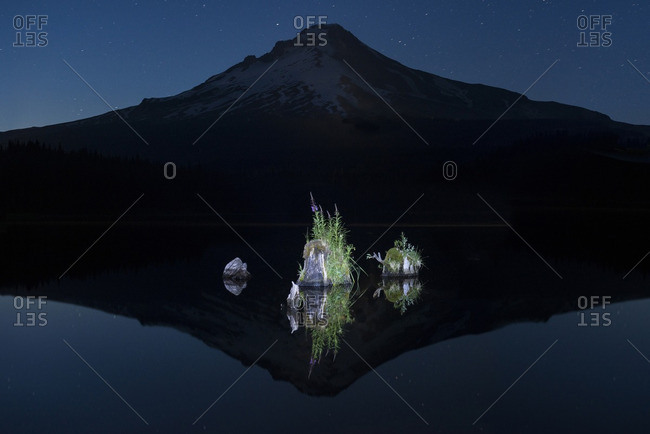 Rocks in calm lake against silhouette mountain at dusk